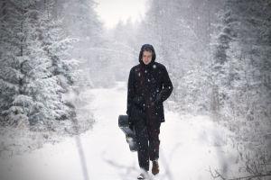 Muusikko Topi Saha kävelee lumisella metsätiellä.