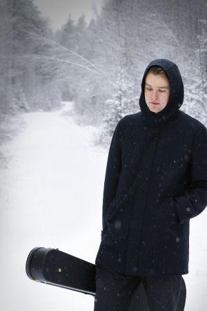 Muusikko Topi Saha seisoo metsätiellä.