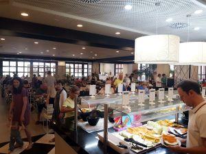 En frukostbuffé och en restaurangmatsal med en massa hotellgäster.