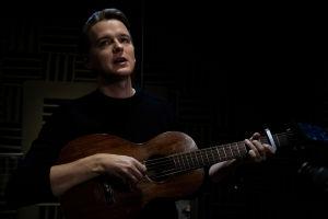 Topi Saha soittaa kitaraa ja laulaa.