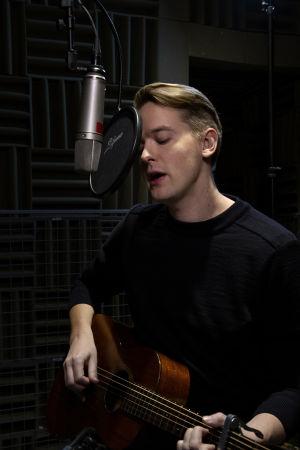 Topi Saha soittaa kitaraa ja laulaa mikrofoniin.