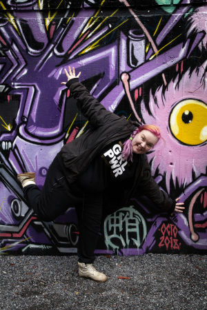 Evaleena Vuorenmaa tasapainottelee yhdellä jalalla graffitiseinän edessä.