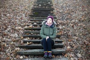 Tiia Valkeapää istuu ulkona portailla. Maassa on paljon lehtiä.