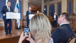 Kostymklädda Lavrov och Haavisto står bakom var sitt podium på en scen, en blond kvinna i publiken filmar Lavrov.