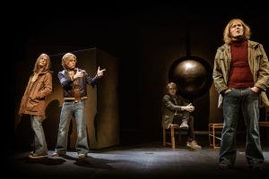 Tre unga skådespelare klädda i sjuttiotalskläder står på en mörk scen. I bakgrunden sitter en äldre man på en stol och betraktar dem.