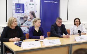 Tre kvinnor och en man sitter vid ett bord med en mikrofon.