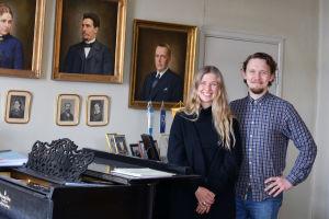 Ida Söderström och Oscar Gräsbäck står vid en svart flygel. På väggen hänger porträtt av olika personer.