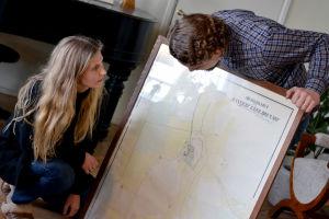 Ida Söderström och Oscar Gräsbäck står vid en tavla med en karta över gården där de bor.