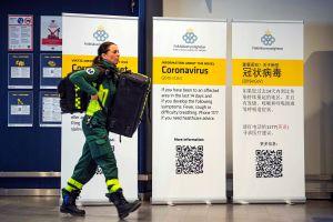 En kvinna i sjukvårdaruniform går förbi coronavirusskyltar.