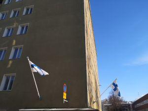 kerrostalo jonka seinällä kaksi suomen lippua tangossa