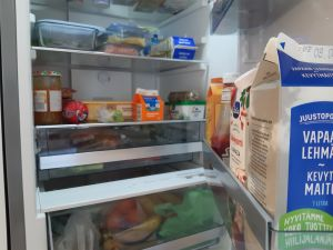 En öppen kylskåpsdörr som visar livsmedlen inuti, mjölk, smör, syltburk, grädde.