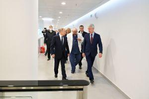 Putin och Sobjanin går i en vit korridor, följda av en läkare i vit läkarrock och en massa människor.