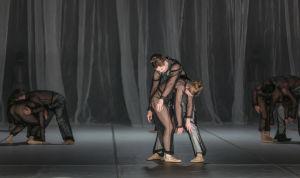Tanssijoita lavalla. Etualalla naistanssija kumartuneena ja miestanssija kumartuneena edellisen ylle. Kuva Kansallisbaletin esityksestä Sciamachy