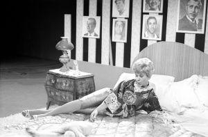 Brita Koivunen loikoo vuoteella Iskelmäkarusellissa vuonna 1962, seinää koristavat miesten muotokuvat.