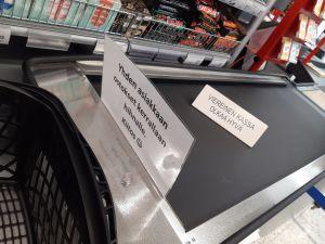 En skylt på rullbandet i livsmedelsaffär med uppmaningen att en kund i taget placerar sina uppköp på bandet.