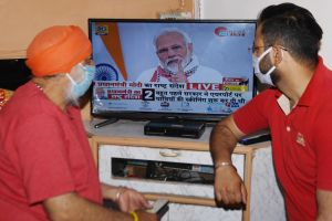 Hälsovårdspersonal tittar på premiärminister Narendra Modi i tv 14.4.2020