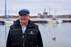 En man i keps ler mot kameran. I bakgrunden bryggor och förtöjda båtar.