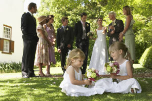 Två små flickor leker på gräsmattan under ett bröllop.