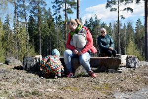 En kvinna med en baby i famnen sitter på en sten. Bredvid leker ett barn i prickig overall. Bakom dem sitter en kvinna och tittar på.