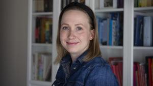 Porträttbild av Sandra Holmgård. Hon har blå skjorta och ett svart diadem.