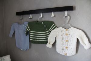 Babykläder som hänger på väggen.