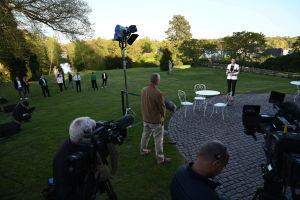 Danmarsk statsminister Mette Frederiksen pratar med journalister utomhus, med flera meters avstånd mellan alla människor.