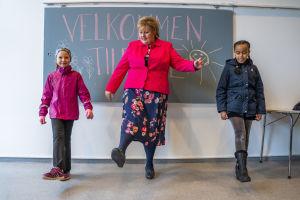 Erna Solberg övar distanshälsningar med två skolelever.