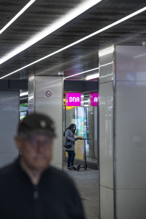 Nainen seisoo sähköpotkulaudan kanssa DNA:n liikkeen edessä. Etualalla kävelee mies.