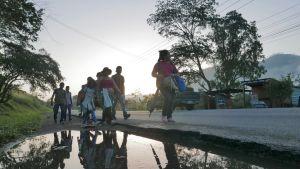 siirtolaiset kävelevät maantiellä