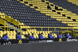Schalke 04-avbytare sitter med säkerhetsavstånd och ansiktsskydd.