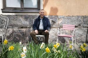 Pertti Simula istuu narsissien takana puutarhapenkillä.