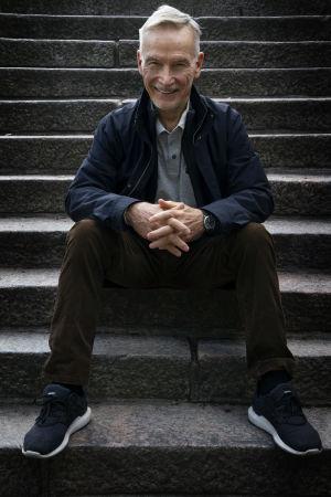 Pertti Simula istuu portailla kädet ristissä.