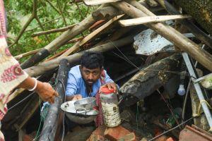 En man med skålar och en burk i handen står i ett hus som förstörts av ett oväder.