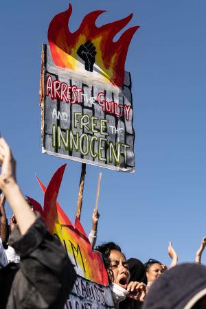 En kvinna håller i en skylt som ser ut att brinna.