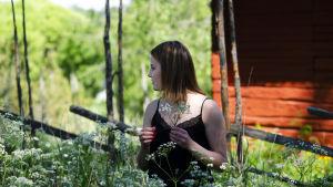 Sofia Svevar framför en gärdesgård