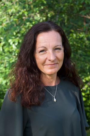 Porträtt på kvinna med mörka kläder och långt hår.
