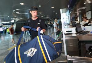 Pekka Rinne lyfter lyfter sin hockeyväska på transportbandet.