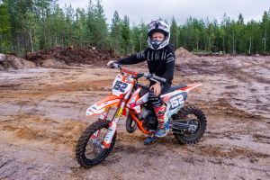 En pojke sitter på en motocrossmotorcykel.