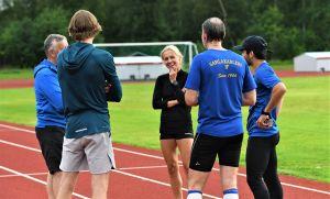 Nina Chydenius samtalar med träningskamrater på sportplan.