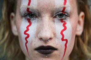 En demonstrant i Moskva har målat sitt ansikte i rött och vitt för att visa sitt stöd för de som protesterar i Belarus.