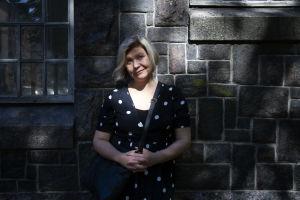Professori Susanna Paasonen seisoo kivimuurin edessä.
