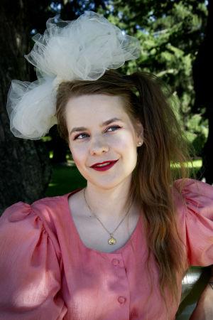Ina Mikkola hymyilee ja katsoo yläviistoon puolikuvassa.