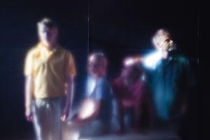 Fyra människor står bakom ett suddigt glas.