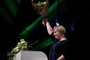Kvinna bakom talarstol. Hon håller i en blombukett. Annika Saarikko i Uleåborg den 5 september efter att ha valts till Centerns ordförande.