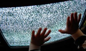 En barn rör en tv med brus på skärmen.