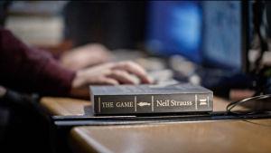 Kirja The Game pöydällä, taustalla tietokone tmv.