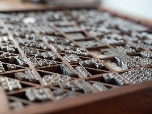 metallisia kirjasimia puulaatikon lokeroissa
