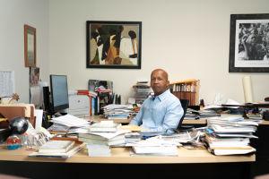 Bryan Stevenson sitter vid sitt arbetsbord, omringad av pappershögar och böcker.