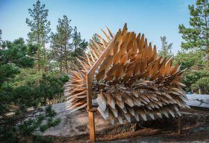 Iso puinen veistos, jossa lehtimäisiä ulokkeita, ympärillä metsää