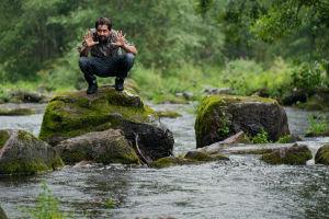 Elokuvaohjaaja Hamy Ramezan ohjaustyössään. Kyykistelee kivellä joessa ja suunnittelee kuvakulmaa.